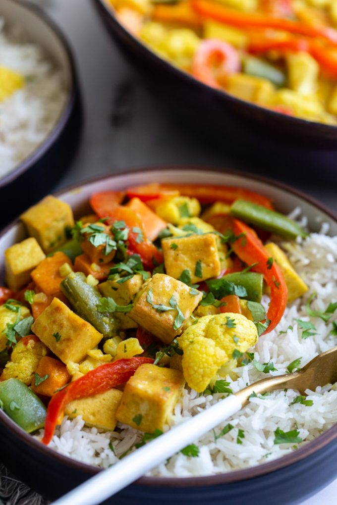 side shot of a bowl of tofu curry that's yellow in color with red bell pepper, tofu, snap peas, and cilantro served over white rice