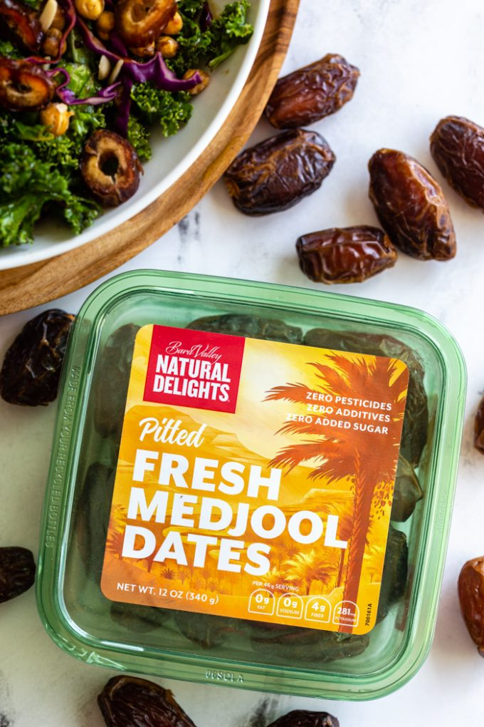 up close shot of a green box of Natural DelightsPitted Fresh Medjool Dates. a kale date salad is in the corner with fresh dates all around