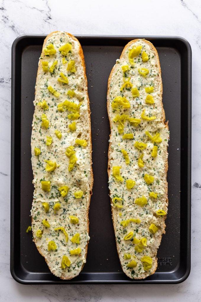 2 metades de pão de alho coberto com pimentão peperoncini picado.  em uma assadeira
