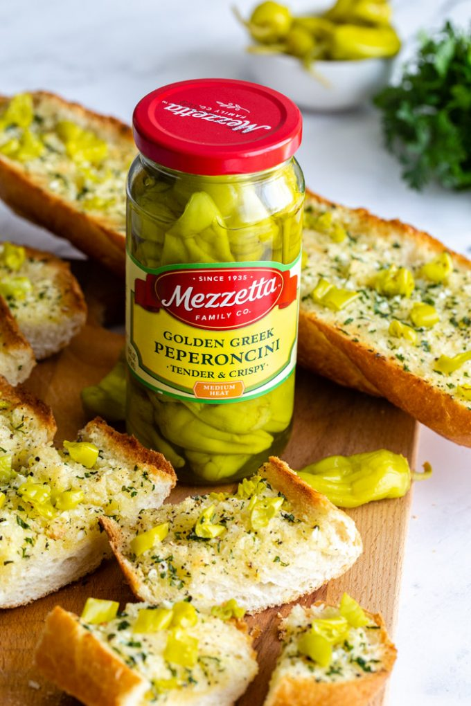 sliced garlic bread topped with chopped peperoncini peppers. focus of the photos is on a jar of mezzetta golden greek peperoncini