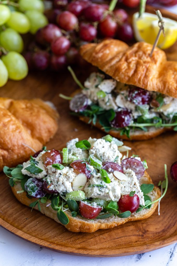 "croissant cut in half and topped with micro green and the tofu ""chicken"" salad with grapes"