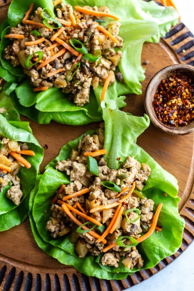 top down shot of vegan lettuce wraps filled with a tofu and mushroom mixture and topped with shredded carrots. all on a round wood board