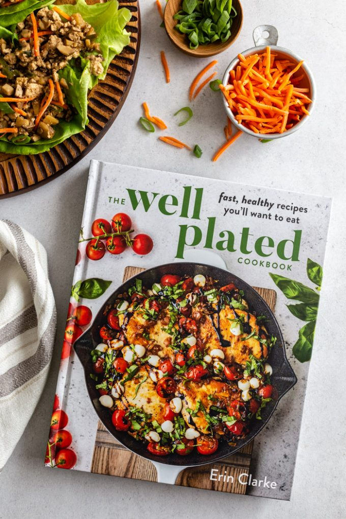 picture of the Well Plated Cookbook with carrots, lettuce wraps, and green onion in the corner