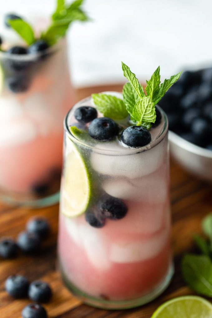 side shot of 2 blueberry mojitos in clear glass with ice and fresh blueberries, mint, and lime garnishing the glass. Both sitting on a wood board with ingredients around