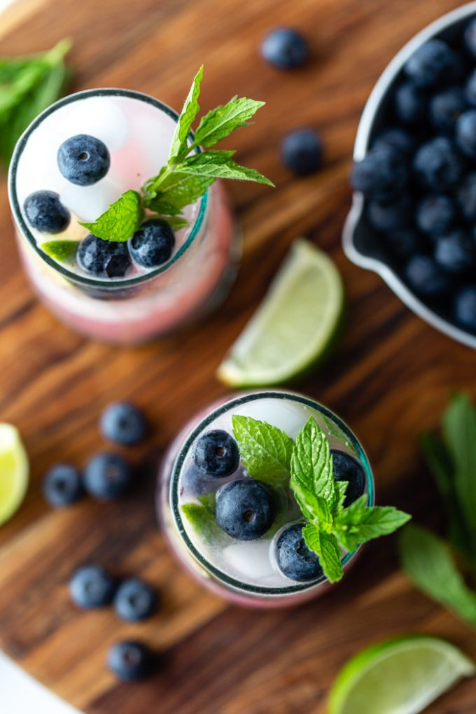 top down shot of 2 blueberry mojitos in clear glass with ice and fresh blueberries, mint, and lime garnishing the glass. Both sitting on a wood board with ingredients around