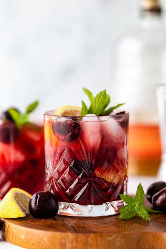 direto na dose de um coquetel de uísque de cereja em uma placa de madeira com cerejas frescas, limão e menta em volta do copo