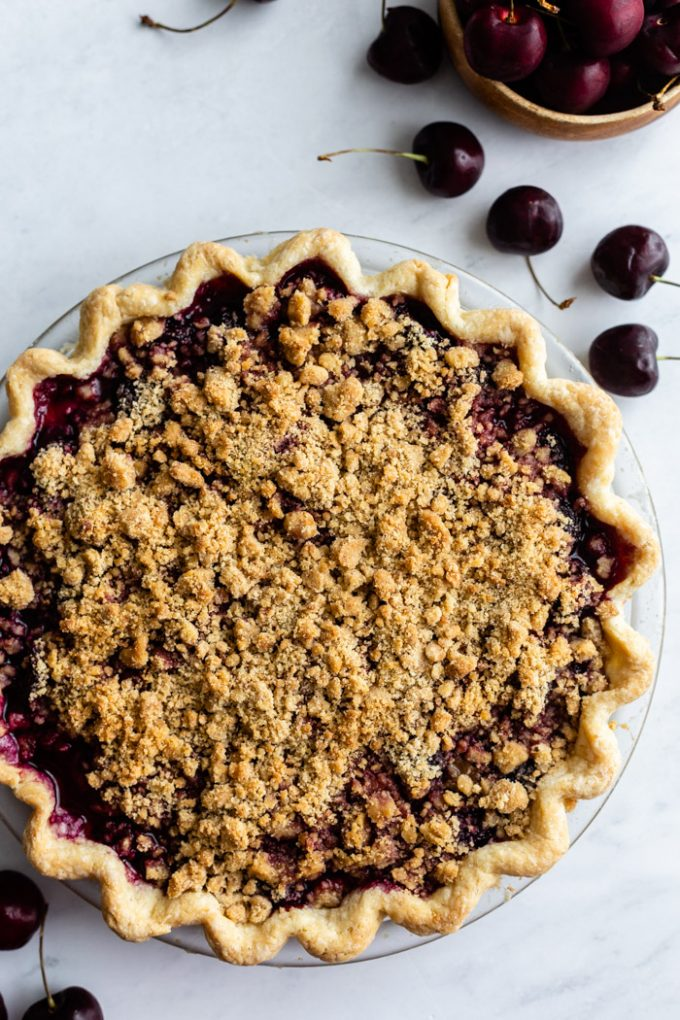 top down shot of a cherry pie with crumble topping. fresh cherries around the scene