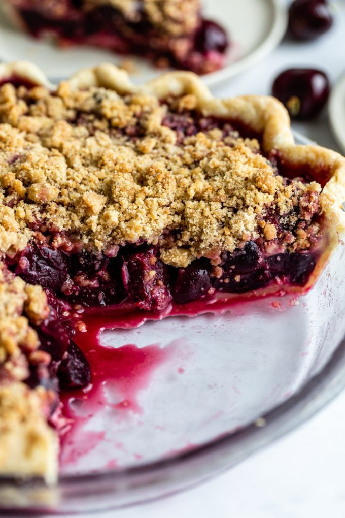side shot of a cherry pie with a crumble topping. a slice is taken out and you can see the inside