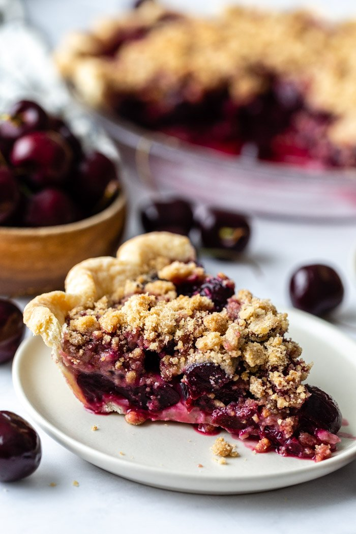 slice of cherry crumble pie on a plate with more slices in the background