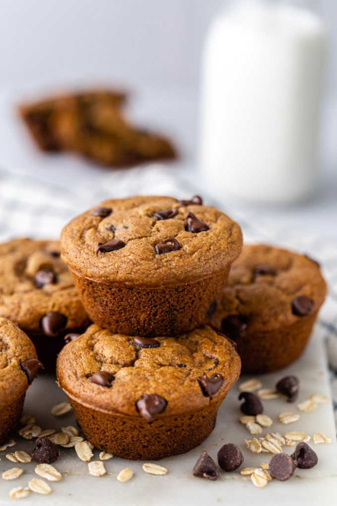 stack of chocolate oat flour muffins with milk and another muffin in the background. Loose chocolate chips and oats around the scene