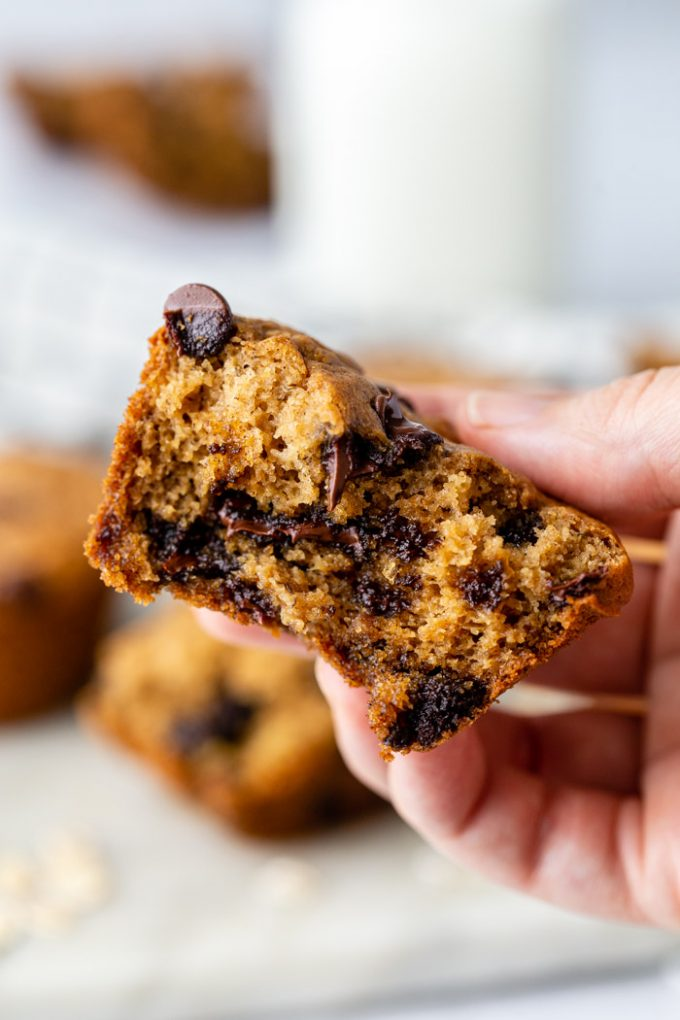up close shot of a hand holding a half eaten chocolate chip oat flour muffin with more muffins and milk in the background
