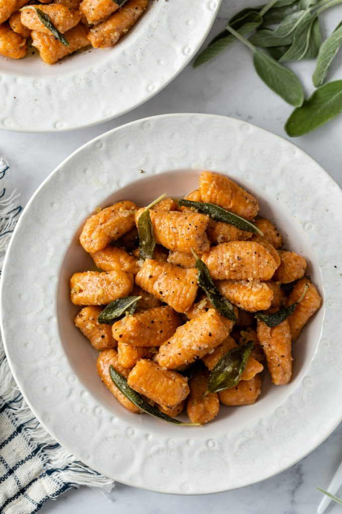 top down shot of sweet potato gnocchi in a sage sauce. In a white bowl with another bowl in the background