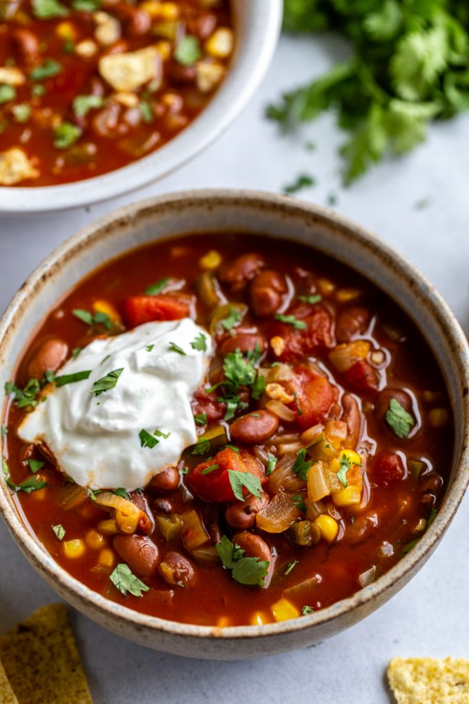 bowl of vegetarian chili with lots of tomatoes and beans. topped with sour cream and cilantro