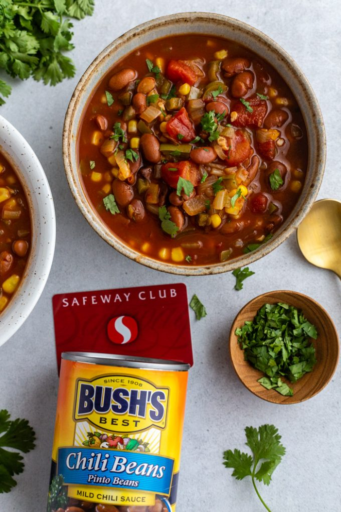 2 bowls of vegetarian chili with cilantro on the table next to it. A can of BUSH'S Chili Beans sitting next to it with a Safeway Club card as well