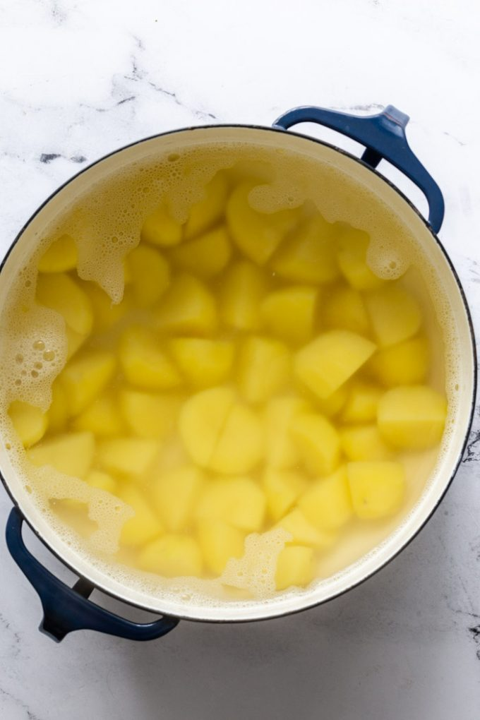 large blue pot filled with diced potatoes covered in water