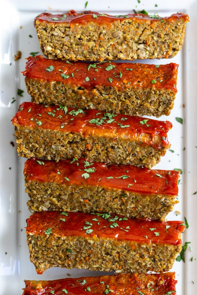 lentil meatloaf topped with ketchup and parsley. Sliced on a white plate