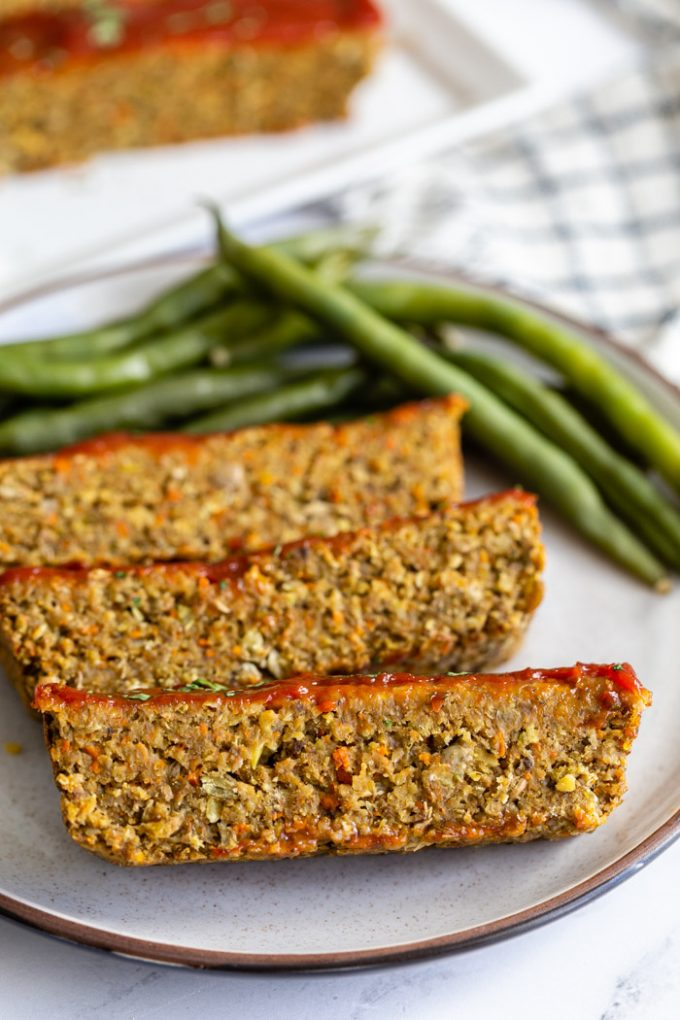 lentil meatloaf topped with ketchup and parsley. Sliced on a plate with green beans