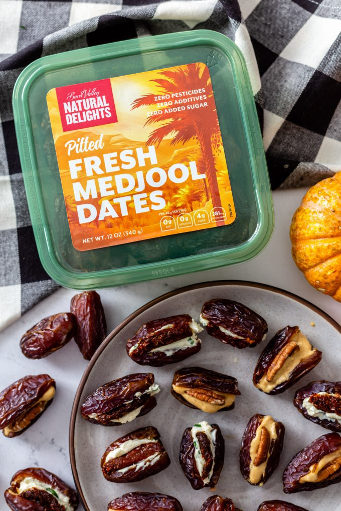 plate filled with stuffed dates and a green natural Delights container filled with pitted fresh medjool dates