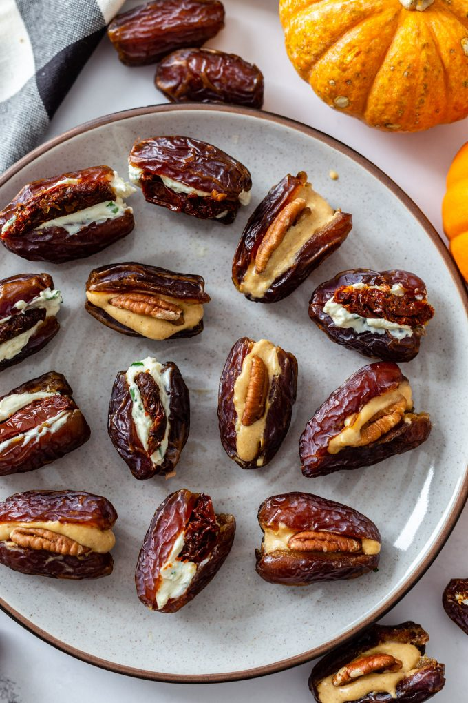 large plate filled with cream cheese stuffed dates. pumpkins in the corner