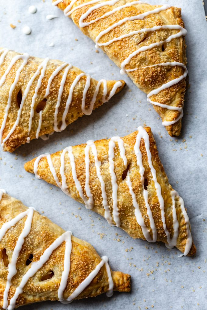 iced apple turnovers on parchment paper