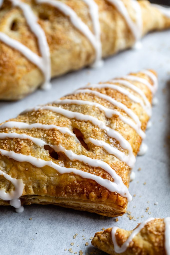 side shot of iced apple turnovers on parchment paper