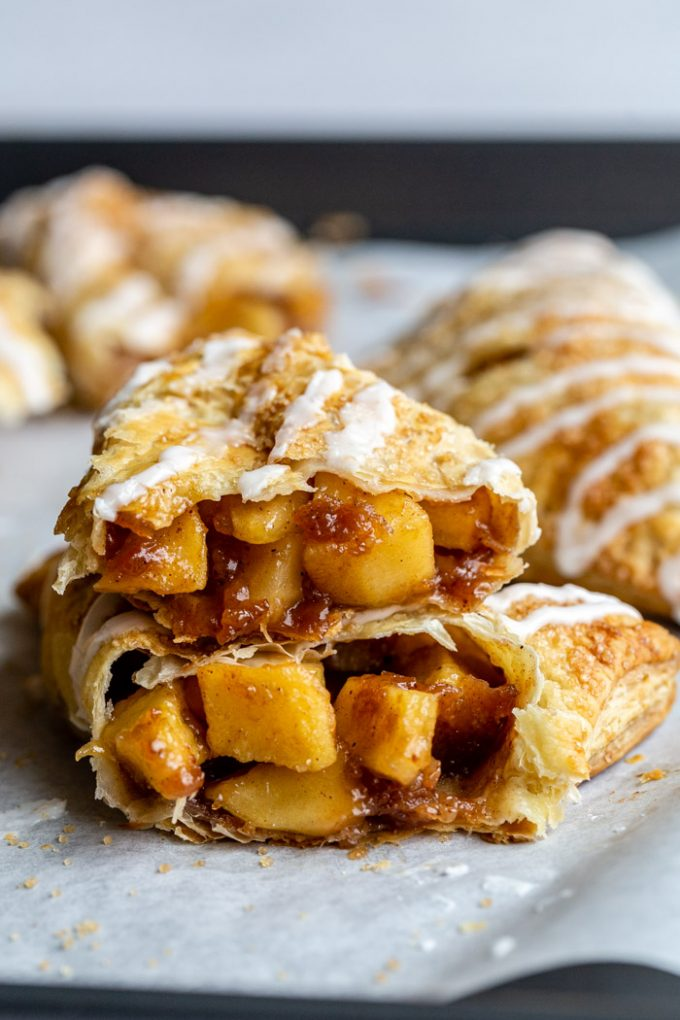 iced apple turnovers on parchment paper where you can see the inside and juicy apples