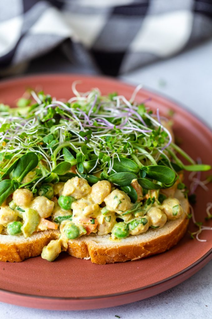 red plate with a curried chickpea salad sandwich on top that's topped with microgreens