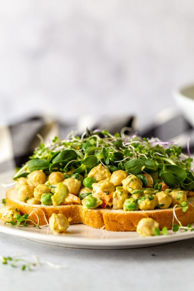 side shot of a curried chickpea sandwich topped with microgreens