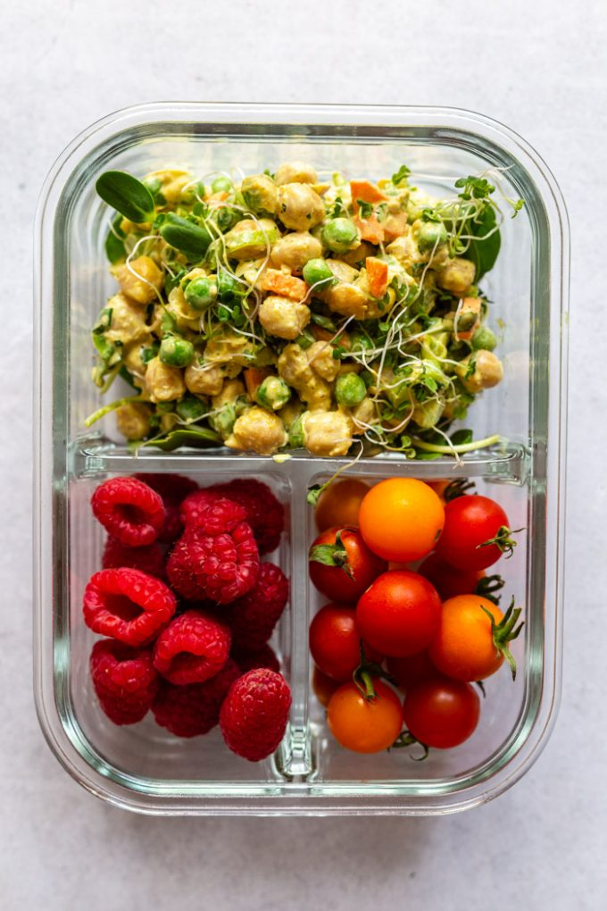 meal prep container with curried chickpea salad in the large spot, raspberries in another slot and cherry tomatoes in another