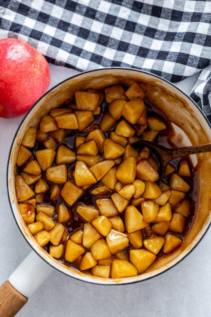 white pot filled with juicy sauted apples