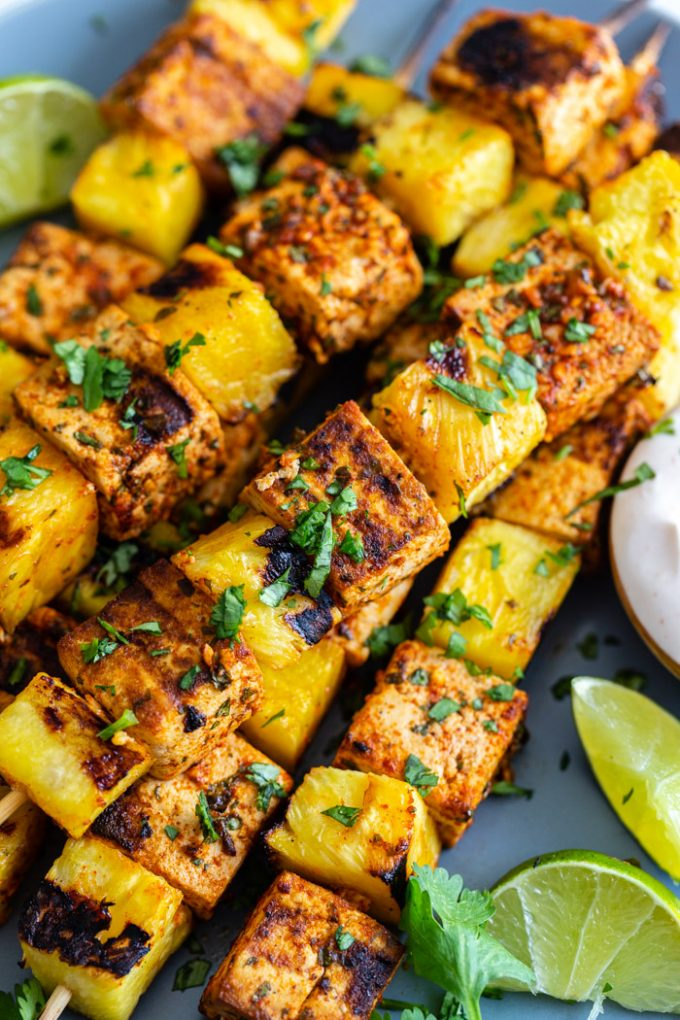 up close shot of grilled skewers with tofu and pineapple sprinkled with cilantro and lime juice