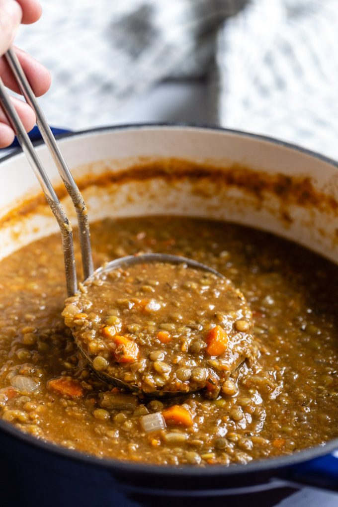 large pot of vegan lentil soup with veggies. a ladle is dipping into the pot to pull up a scoop full of the soup