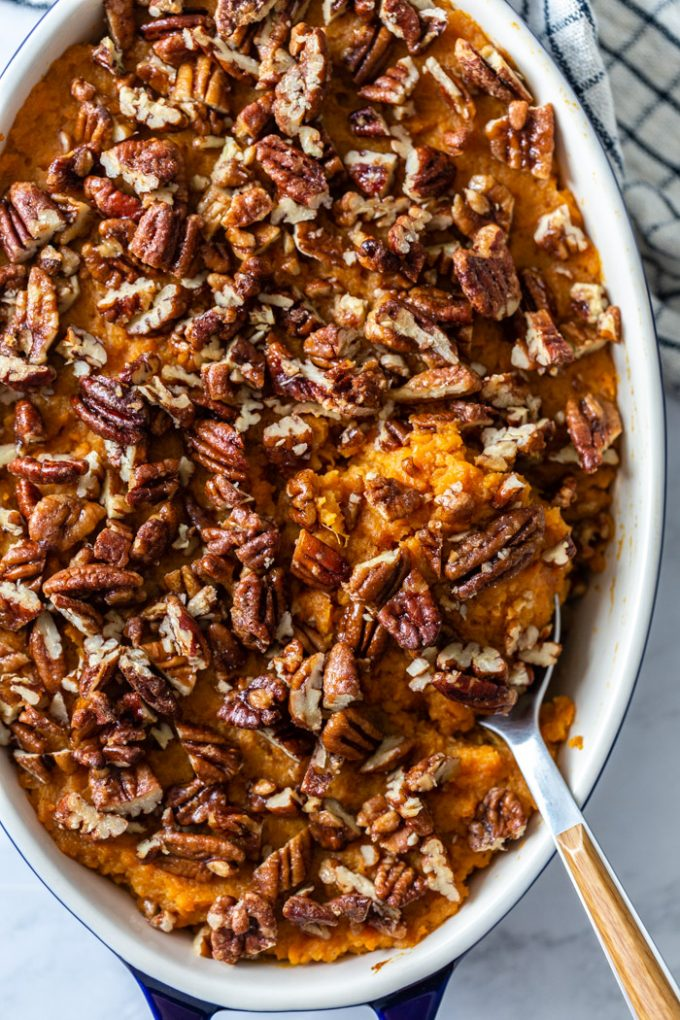 top down shot of sweet potato casserole in a casserole pan topped with candied pecans. a spoon hanging out the side