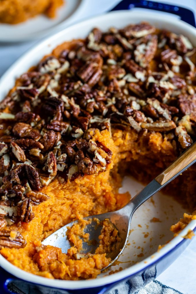 side shot of sweet potato casserole in a casserole pan topped with candied pecans. a portion of the casserole is gone and a spoon is in the dish