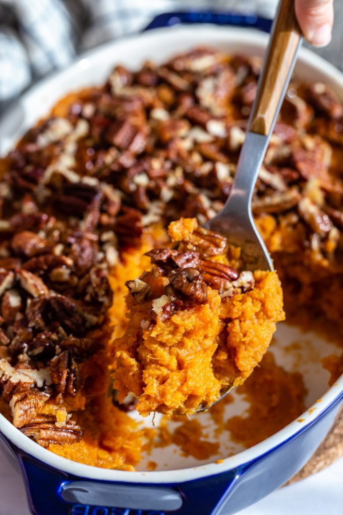 sweet potato casserole topped with candied pecans being pulled out of a casserole dish