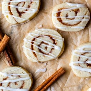 top down shot of cinnamon roll sugar cookies on parchment paper and drizzled with frosting
