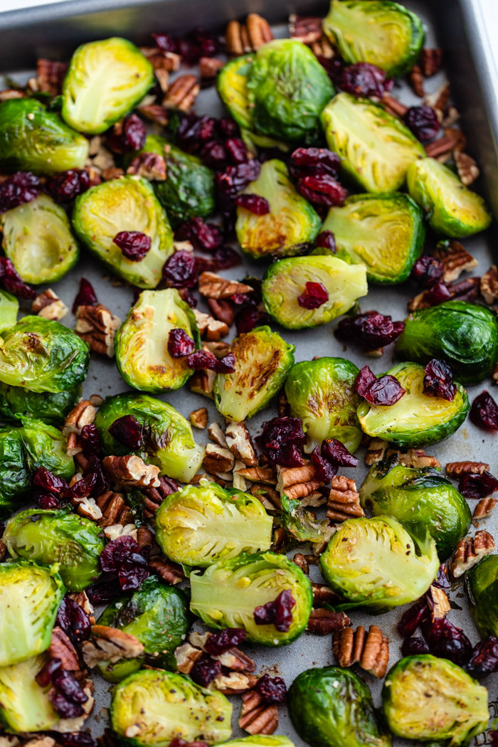 baking tray filled with roasted brussels sprouts and tossed with pecan pieces and dried cranberries