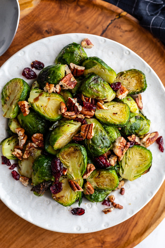bowl of cooked brussels sprouts in a white bowl mixed with pecan pieces and dried cranberries