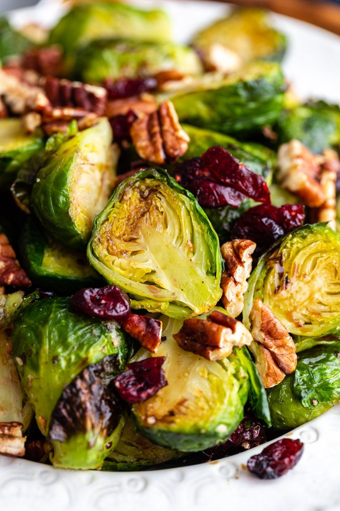 bowl full of roasted brussels sprouts mixed with dried cranberries and pecans