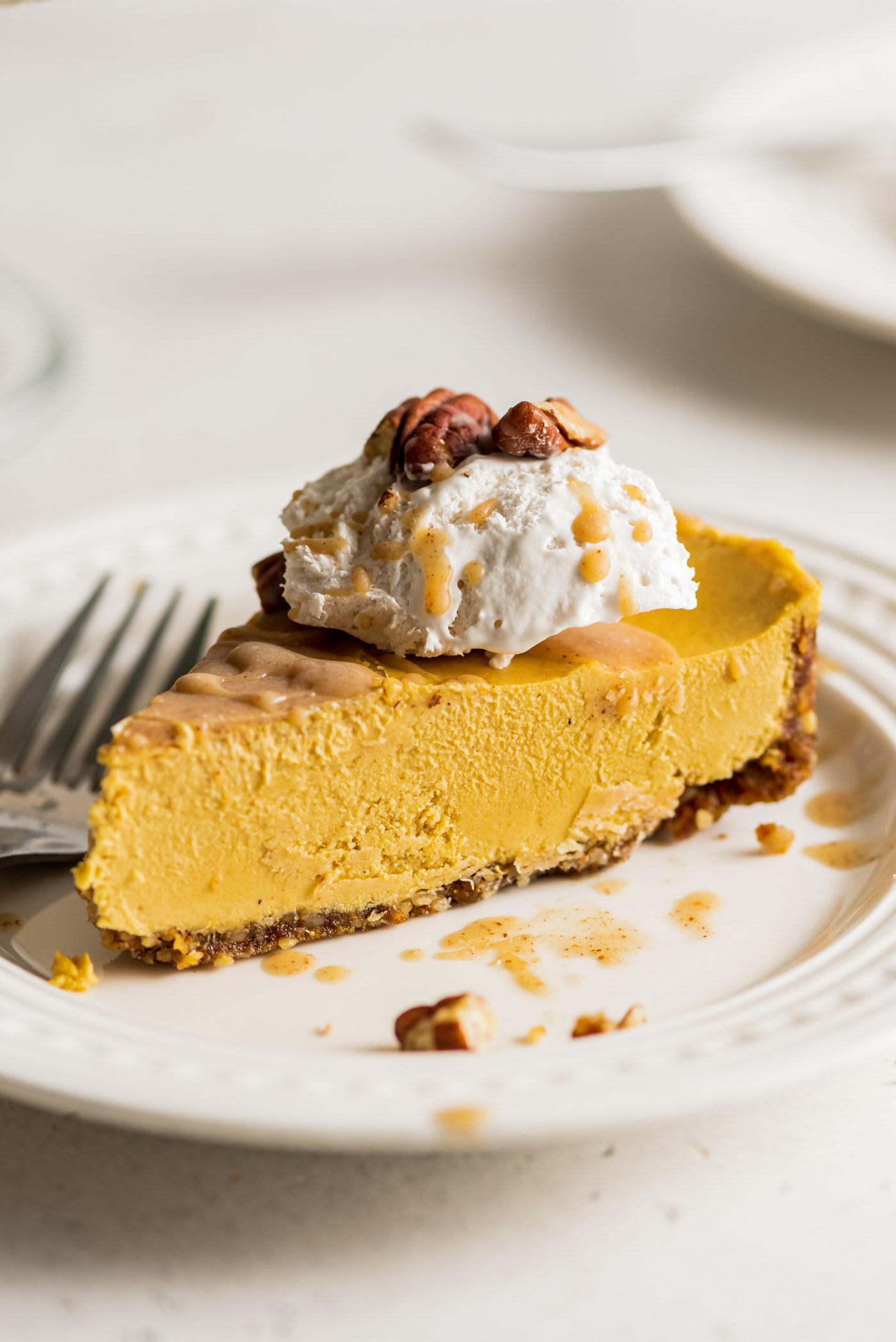 slice of pumpkin cheesecake on a plate topped with whipped cream