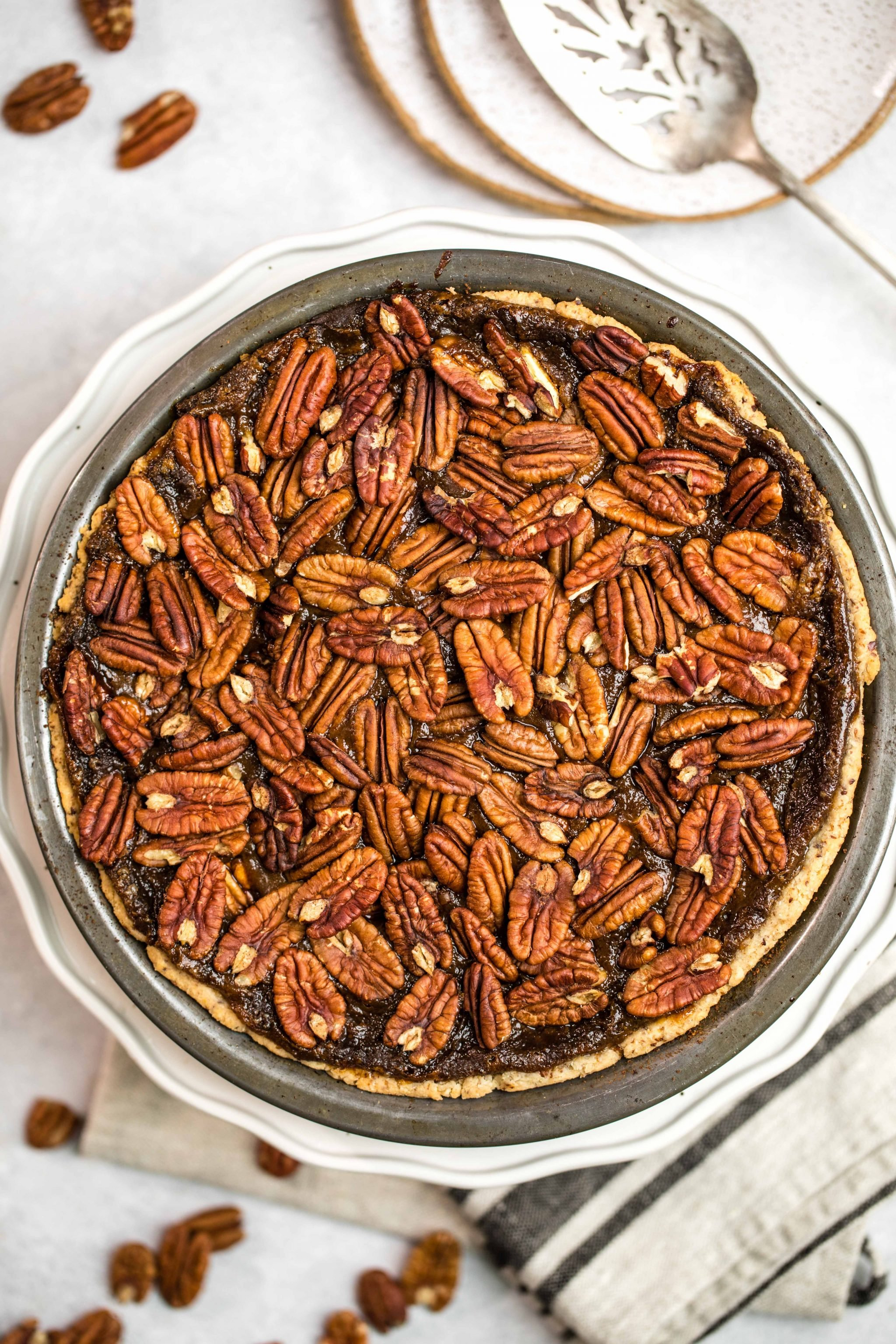 vegan pecan pie on a table with pecans around