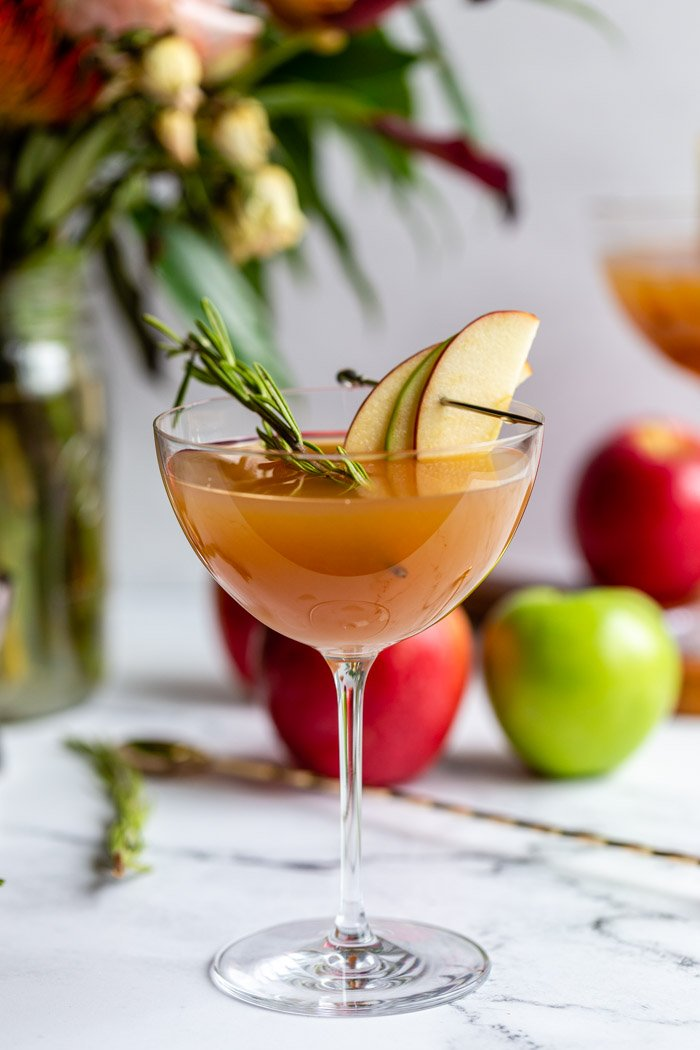 apple cider cocktail in a cocktail glass garnished with apple slices and rosemary with flowers and apples in the background