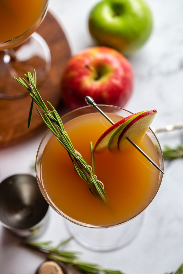 apple cider cocktail in a cocktail glass garnished with apple slices and rosemary and apples in the background