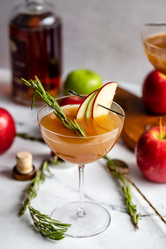 apple cider cocktail in a cocktail glass garnished with apple slices and rosemary with liquor bottle and apples in the background