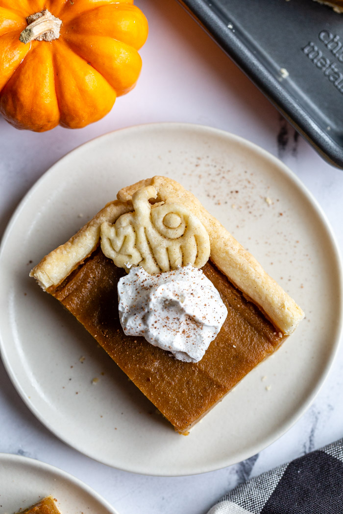 square slice of pumpkin pie topped with a pie crust pumpkin and whipped cream. a small orange pumpkin in the corner of the shot