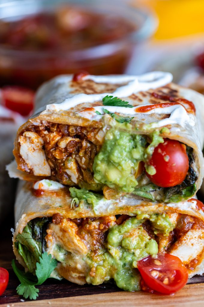burrito cut in half so you can see the inside filled with spicy tofu, guacamole, lettuce and tomatoes. more burritos in the background