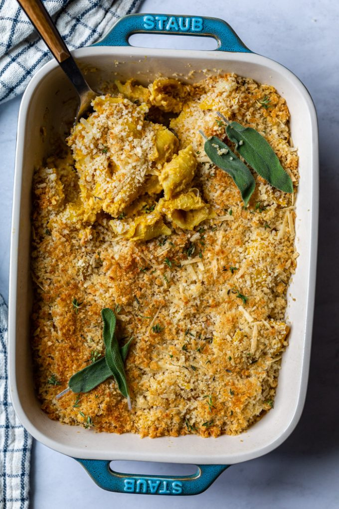 teal colored casserole dish filled with baked vegan mac and cheese and fresh herbs