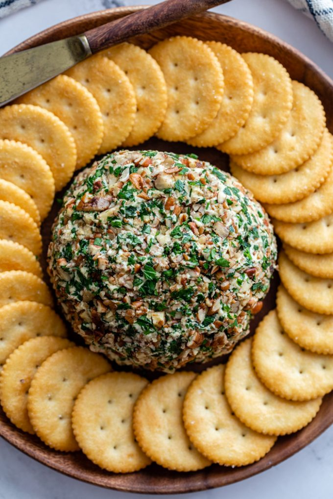 cheeseball with a ring of crackers around it on a serving plate