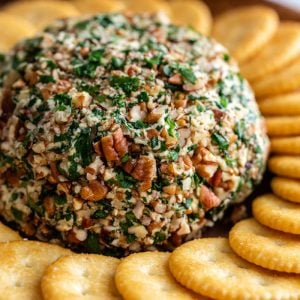 vegan cheeseball covered in chopped pecans and served with Ritz crackers
