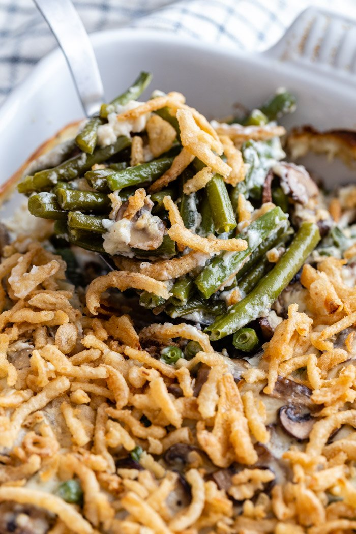 up close shot of green bean casserole in a baking dish and covered with crispy onions